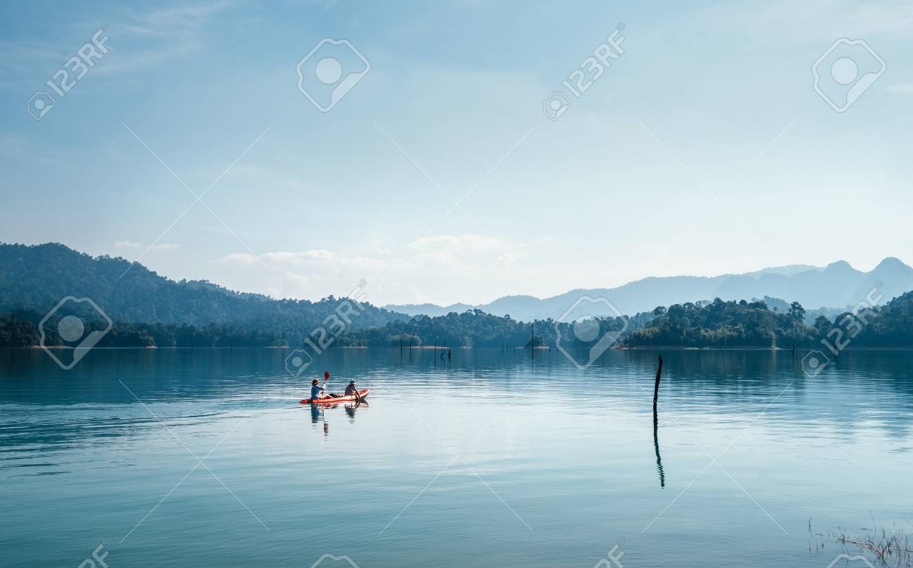 Mother and son floating on kayak together on calm water of Cheow Lan lake in Thailand - 121462509