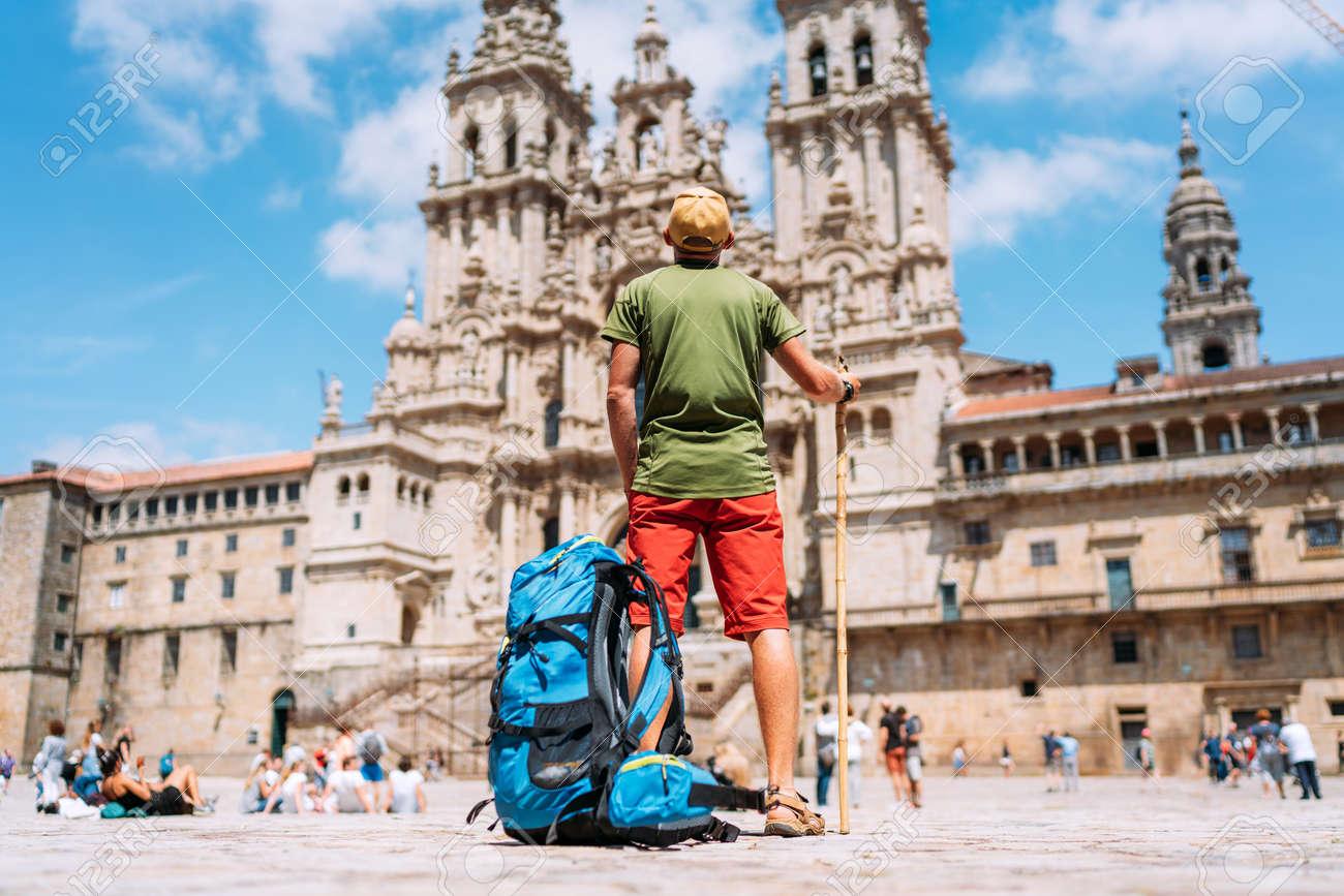 Young backpacker man pilgrim standing on the Obradeiro square (plaza) - the main square in Santiago de Compostela as a end of his Camino de Santiago pilgrimage. - 132067320