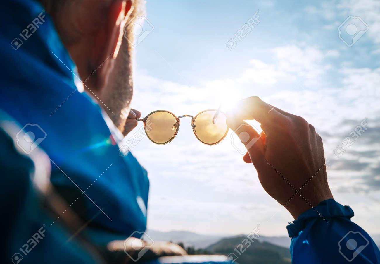 Backpacker man looking at bright sun through polarized sunglasses enjoying mountain landscape. - 130603213