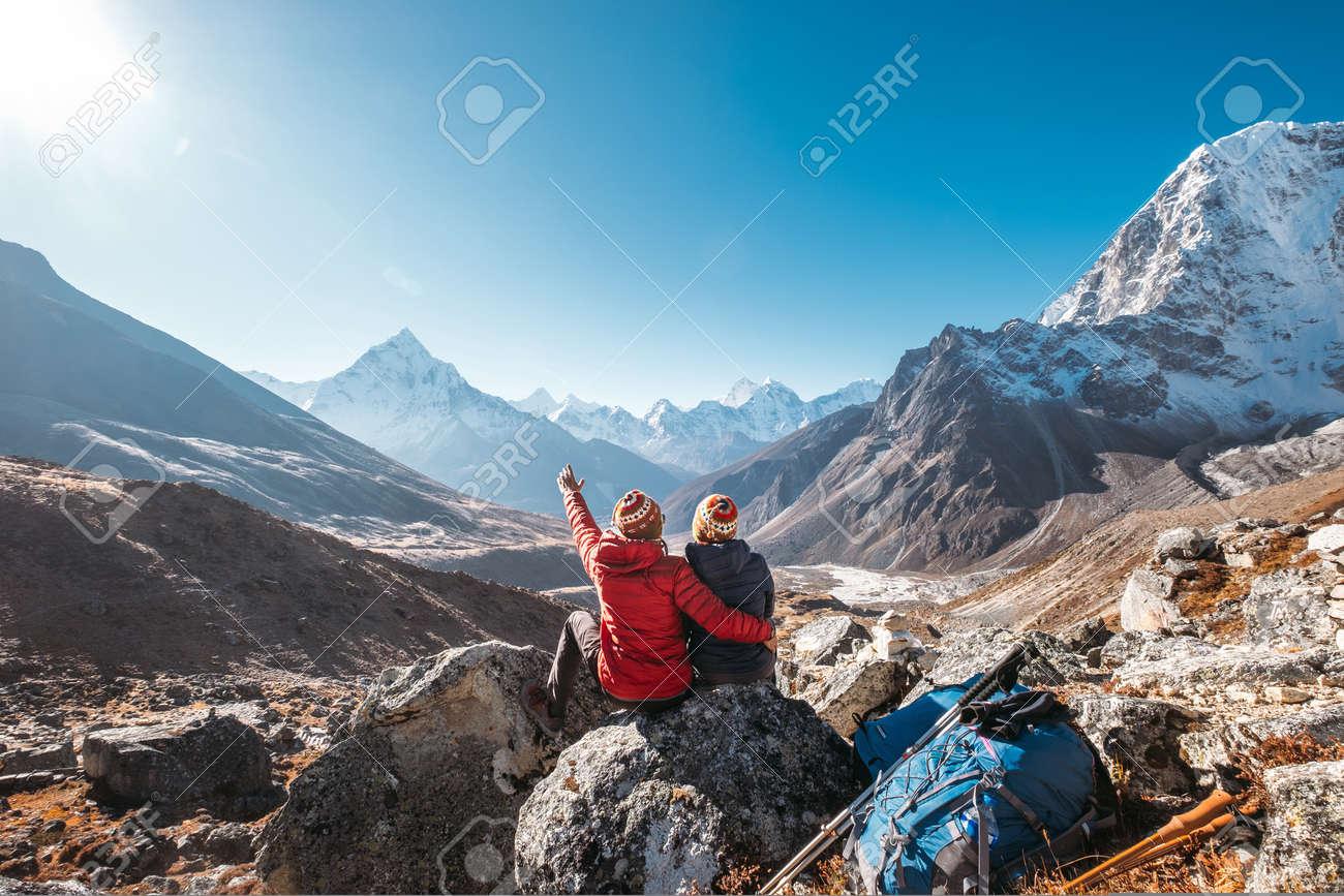 Couple having a rest on Everest Base Camp trekking route near Dughla 4620m. - 134360827