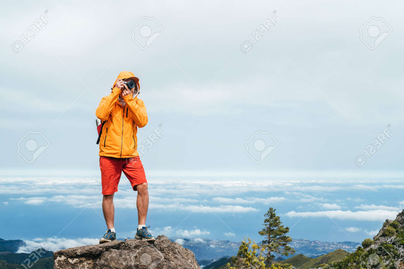 Young adult caucasian man dressed sporty clothes with backpack taking a picture from Pico Ruivo mount 1861m - the highest peak on the Madeira Island,Portugal. Active vacation concept image. - 144553967