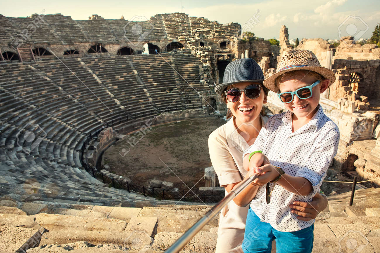 Mother with son smiling to camera taking a selfie photo in antique theatre using a selfie stick. Traveling around the world with kids concept image. - 148012841