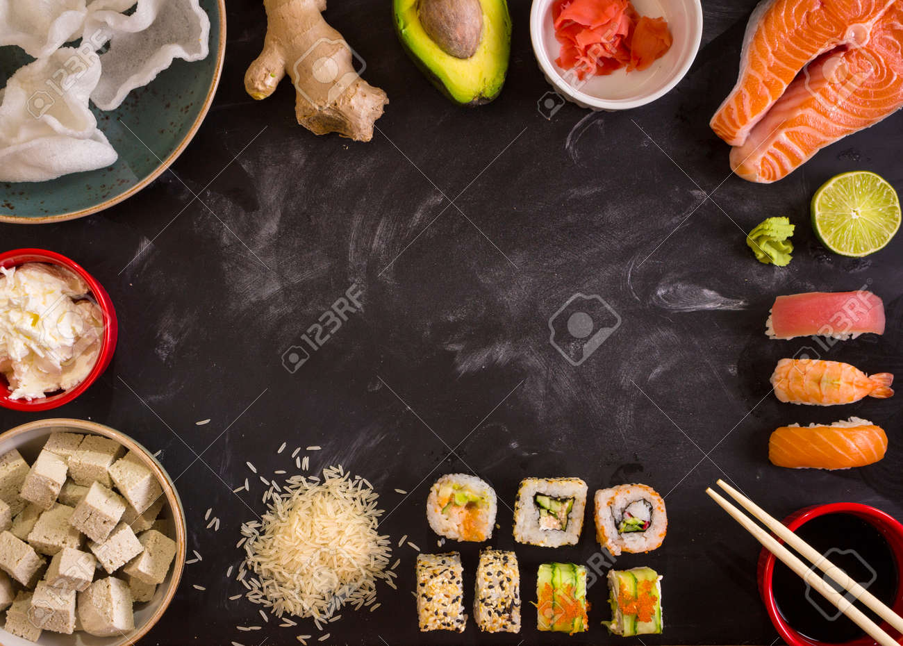 Overhead shot of sushi and ingredients on dark background. Sushi rolls, nigiri, raw salmon steak, rice, cream cheese, avocado, lime, pickled ginger (gari), raw ginger, wasabi, soy sauce, nori, сhopsticks. Asian food background. Space for text - 43320313