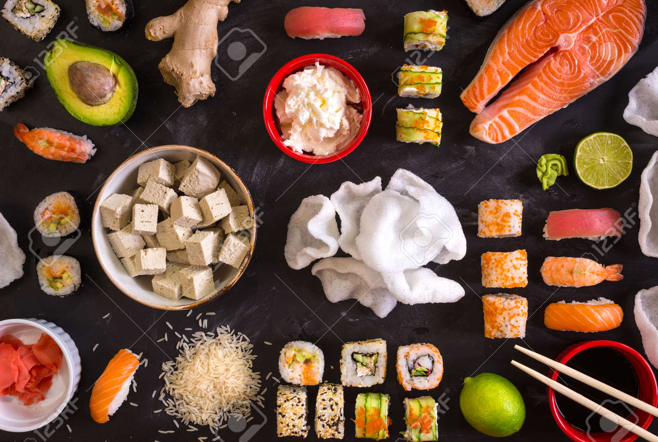 Set of traditional japanese food on a dark background. Sushi rolls, nigiri, raw salmon steak, rice, cream cheese, avocado, lime, pickled ginger (gari), raw ginger, wasabi, soy sauce, nori, сhopsticks. Asian food frame. Dinner party. Space for text - 43320315