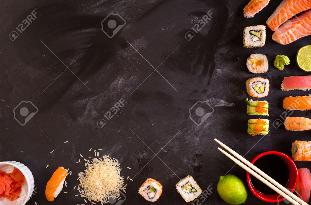Overhead shot of sushi and ingredients on dark background. Sushi rolls, nigiri, raw salmon steak, rice, cream cheese, avocado, lime, pickled ginger (gari), raw ginger, wasabi, soy sauce, nori, сhopsticks. Asian food background. Space for text - 43320319