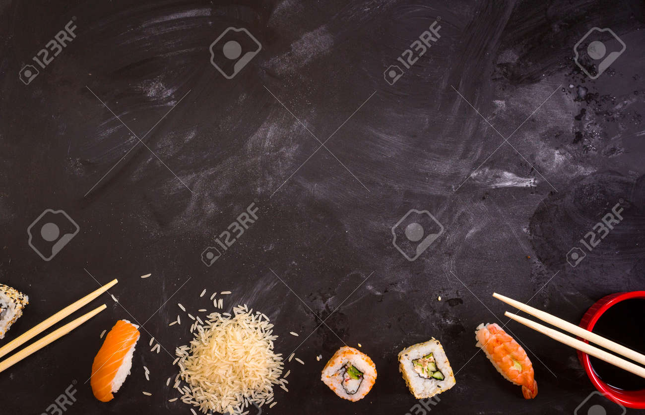 Overhead shot of sushi on dark background. Sushi rolls, nigiri, rice, soy sauce, сhopsticks. Asian food background. Space for text. Sushi set - 43320468