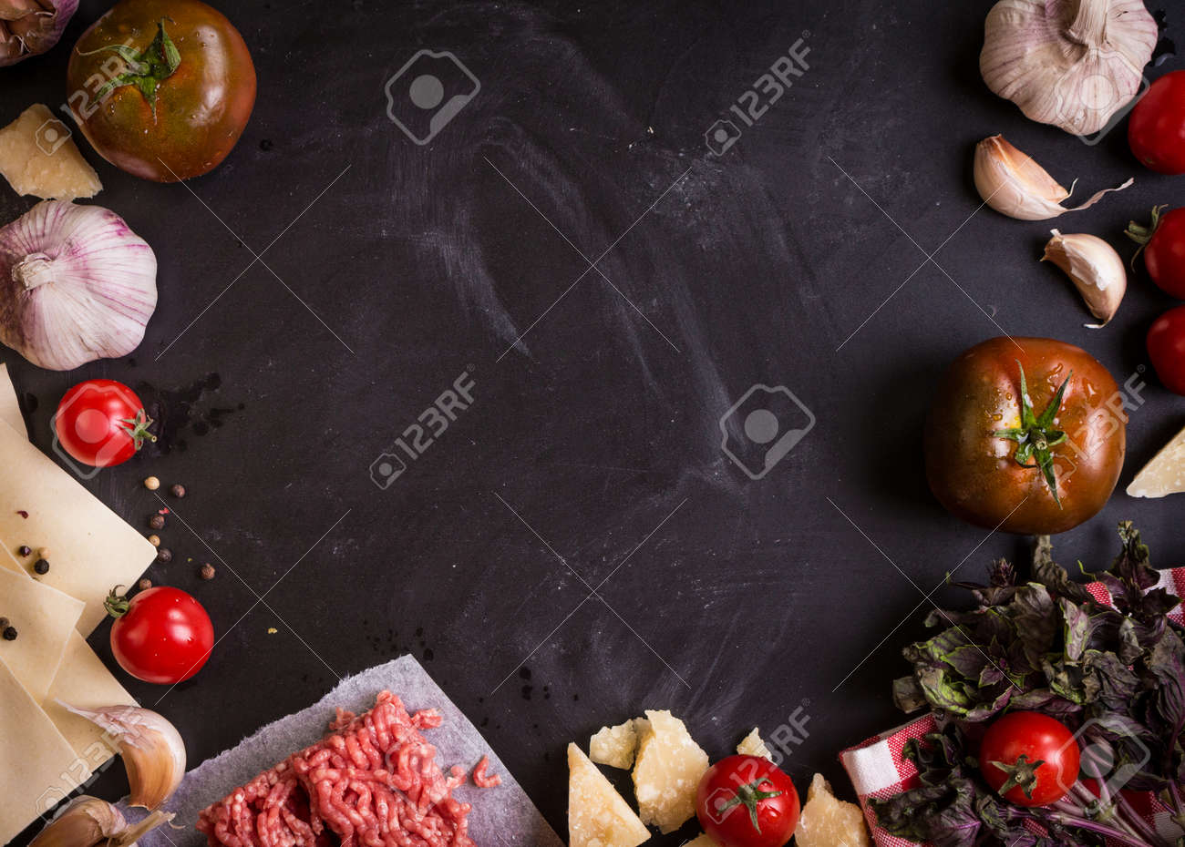 Set of ingredients for italian lasagne. Black food background with free space for text. Pasta, tomatoes, fresh ground meat, parmesan, mozzarella, basil, garlic on a rustic chalkboard. Overhead - 46103147