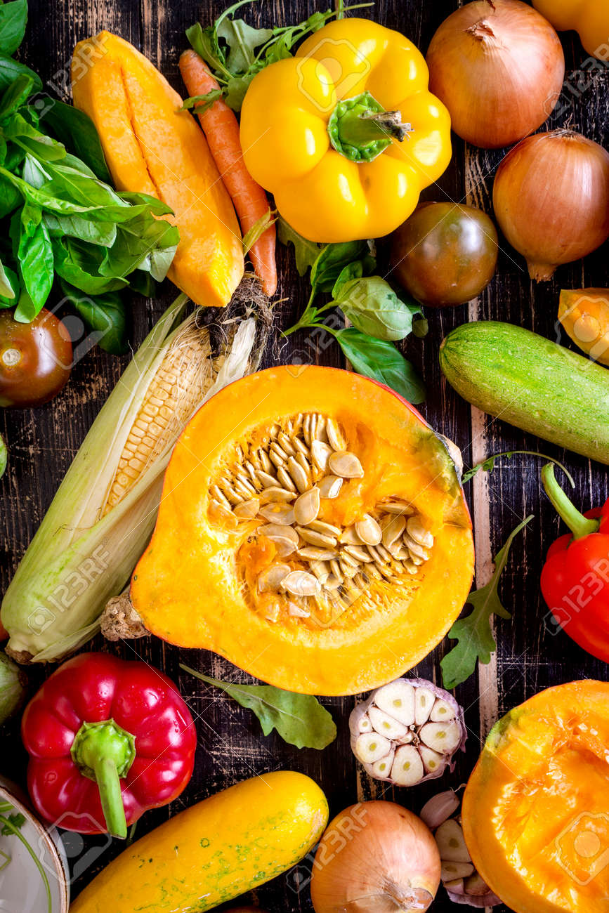 Fresh vegetables scattered on a old rustic dark textured table. Autumn background. Healthy eating. Sliced pumpkin, zucchini, squash, bell peppers, carrots, onions, cut garlic, tomatoes, eggplant, corn cob, rucola and basil. Top view - 47701526