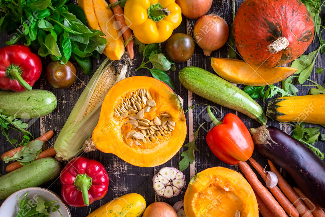 Fresh vegetables scattered on a old rustic dark textured table. Autumn background. Healthy eating. Sliced pumpkin, zucchini, squash, bell peppers, carrots, onions, cut garlic, tomatoes, eggplant, corn cob, rucola and basil. Top view - 47701658