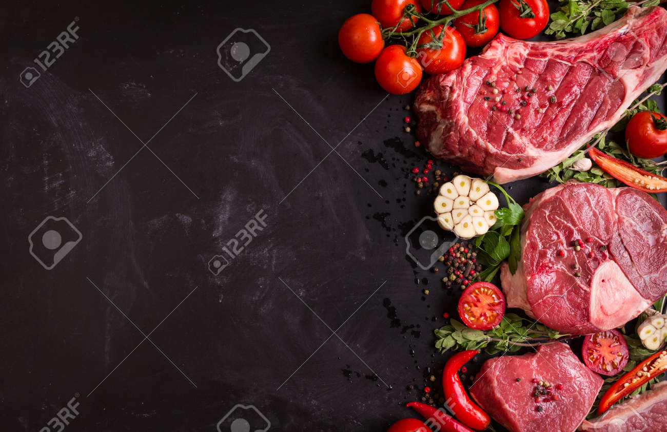 Raw juicy meat steaks ready for roasting on a black chalk board background. Rib eye steak on the bone, veal shank (ossobuco), fillet with cherry tomatoes, hot pepper and herbs. Space for text - 52916624