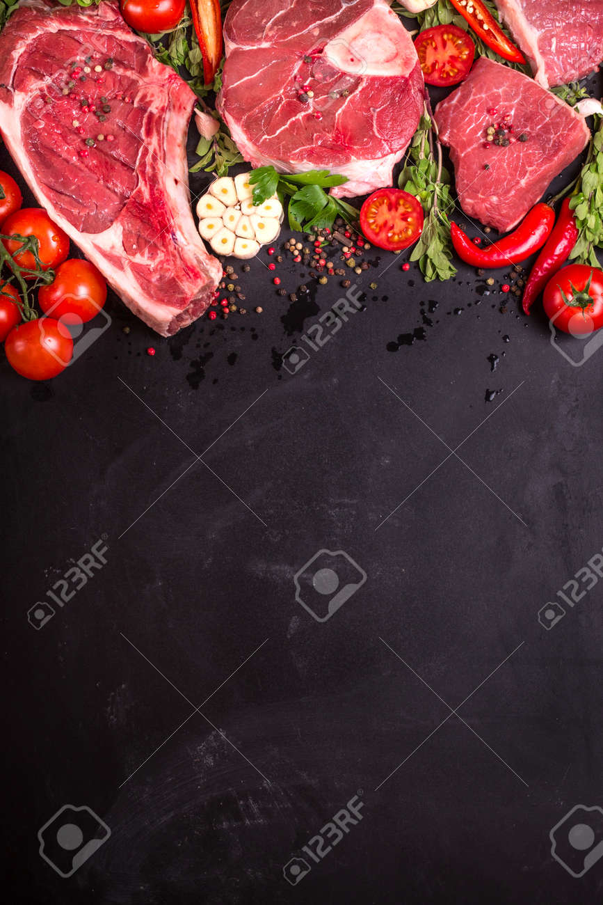Raw juicy meat steaks ready for roasting on a black chalk board background. Rib eye steak on the bone, veal shank (ossobuco), fillet with cherry tomatoes, hot pepper and herbs. Space for text - 52916701