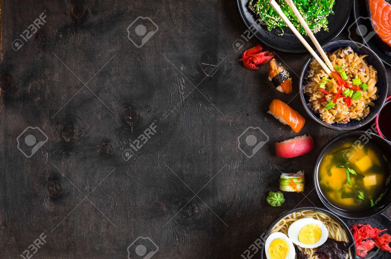 Sushi and japanese food on dark background. Sushi rolls, hiyashi wakame, miso soup, ramen, fried rice with vegetables, nigiri, salmon steak, soy sauce, ?hopsticks. Asian/Japanese food frame. Overhead - 55247875