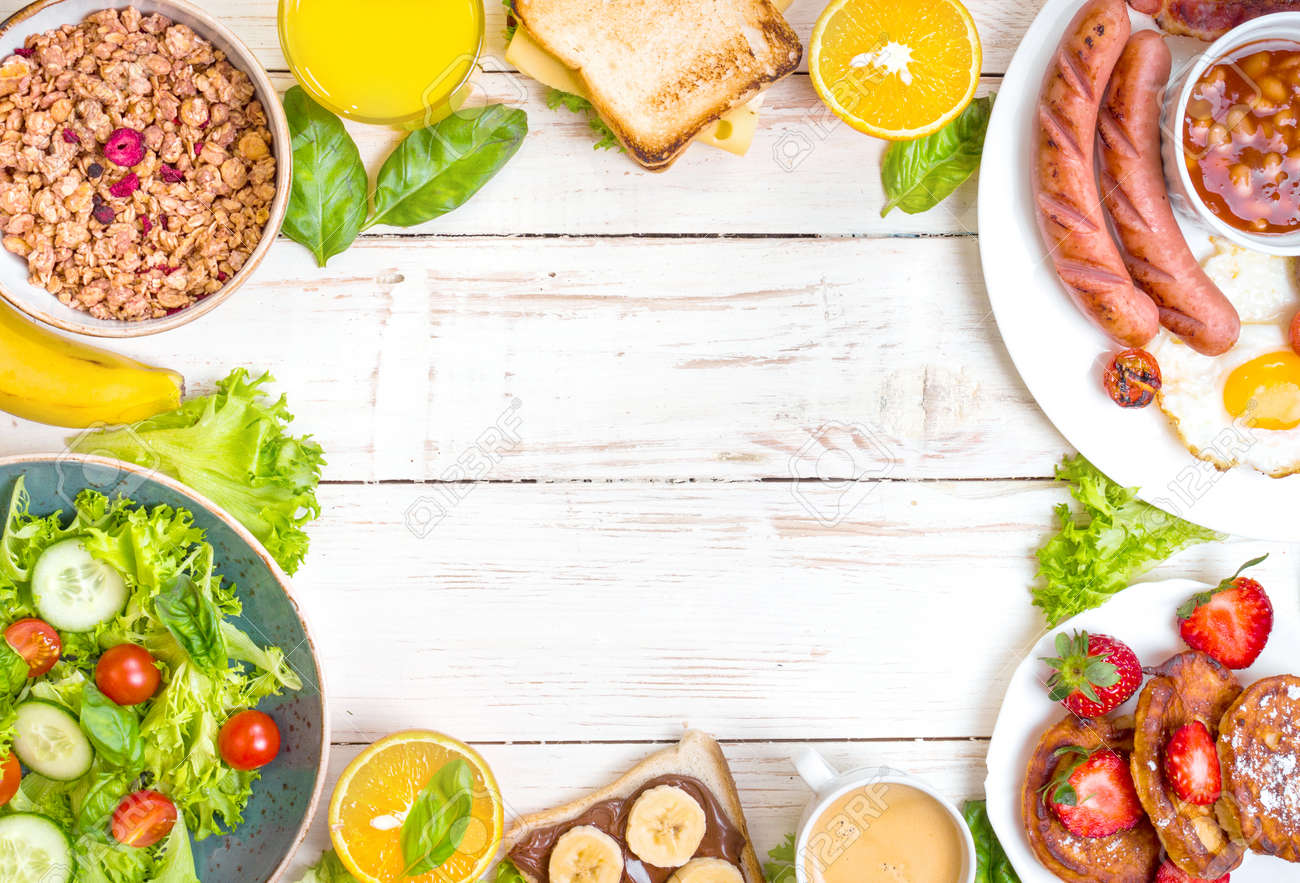 Assortment of breakfast choices. English breakfast, sausages, fried eggs, bacon, salad, granola, cheese sandwich, pancakes, chocolate cream and banana toast, coffee, fresh orange juice. Space for text - 55247884