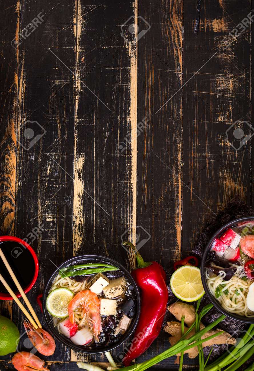 Table served with asian noodle soups in a black bowls with chopsticks, soy sauce, sliced lime, ginger on a dark textured wooden background. Space for text. Asian style dinner. Ingredients for cooking - 55248040