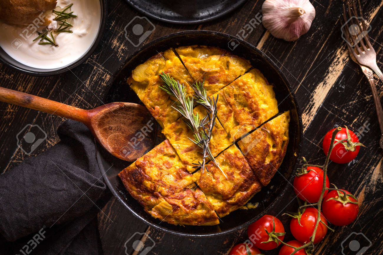 Tortilla de patatas in a pan with garlic sauce aioli and fresh tomatoes cherry. Traditional spanish dish. Omelette with eggs, potatoes and onion. Rustic black background. Top view - 55248225