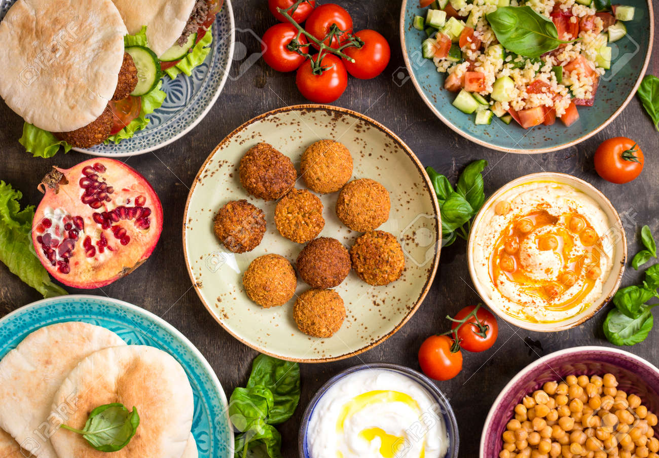 Table served with middle eastern traditional dishes. Bowl with falafel, doner kebap, vegetarian pita, hummus, tabbouleh bulgur salad, chickpea, olive oil dip, pomegranate. Top view. Dinner party - 58767718