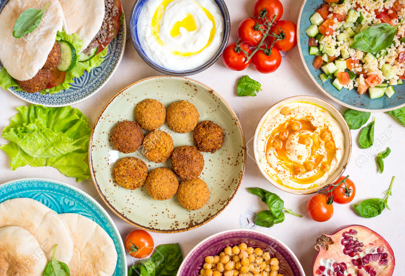 Table served with middle eastern traditional dishes. Bowl with falafel, doner kebap, vegetarian pita, hummus, tabbouleh bulgur salad, chickpea, olive oil dip, pomegranate. Top view. Dinner party - 58767556