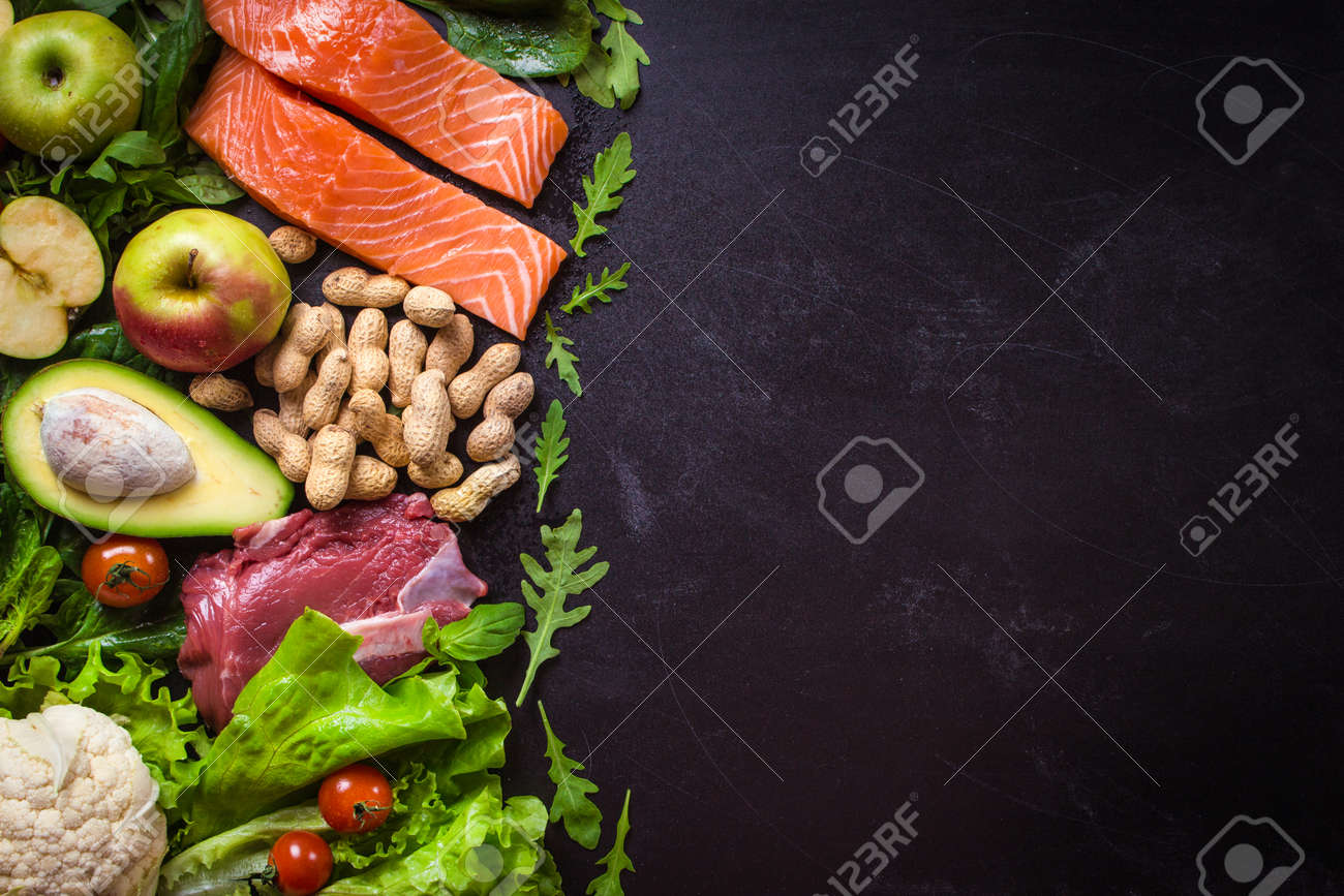Fresh vegetables, fruits, fish, meat, nuts on black chalk board background. ?auliflower, avocado, apples, tomatoes, salmon, beef, spinach, herbs. Diet/healthy/paleo food. Ingredients. Space for text - 68744801