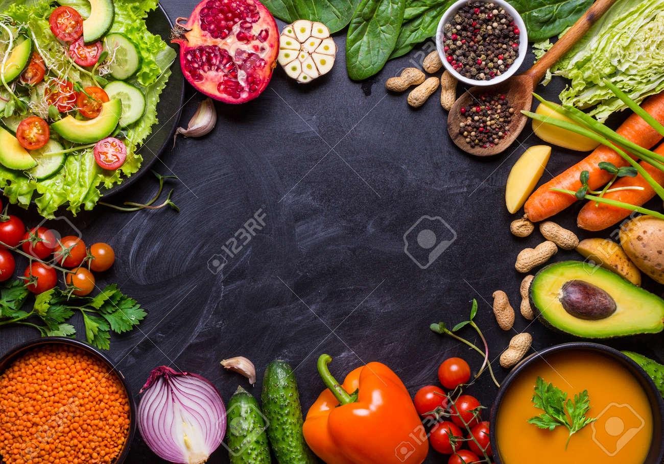 Vegan food and dishes. Pumpkin soup, salad, vegetables, fruits, lentils on rustic black chalk board background. Healthy, clean eating concept. Vegan or gluten free diet. Space for text. Vegan dinner - 71416970