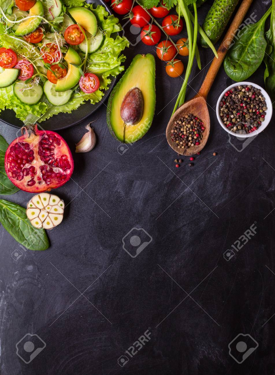 Ingredients for making salad on rustic black chalk board background. Vegetable salad in bowl, avocado, tomato, cucumber, spinach. Healthy, clean eating concept. Vegan or gluten free diet. Copy space - 71416943