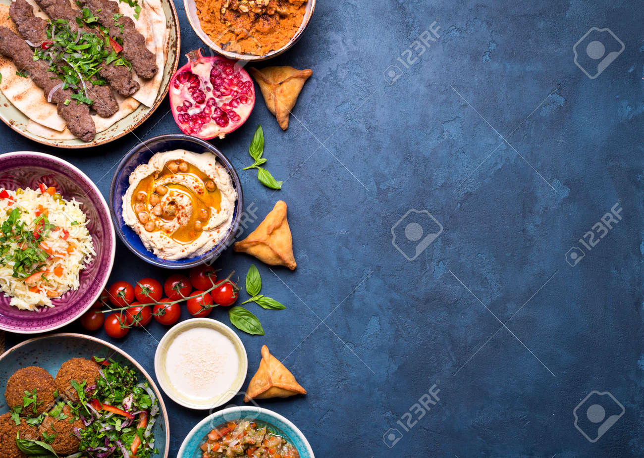 Middle eastern or arabic dishes and assorted meze on concrete rustic background. Meat kebab, falafel, baba ghanoush, hummus, sambusak, rice, tahini, kibbeh, pita. Halal food. Space for text. Top view - 71417050