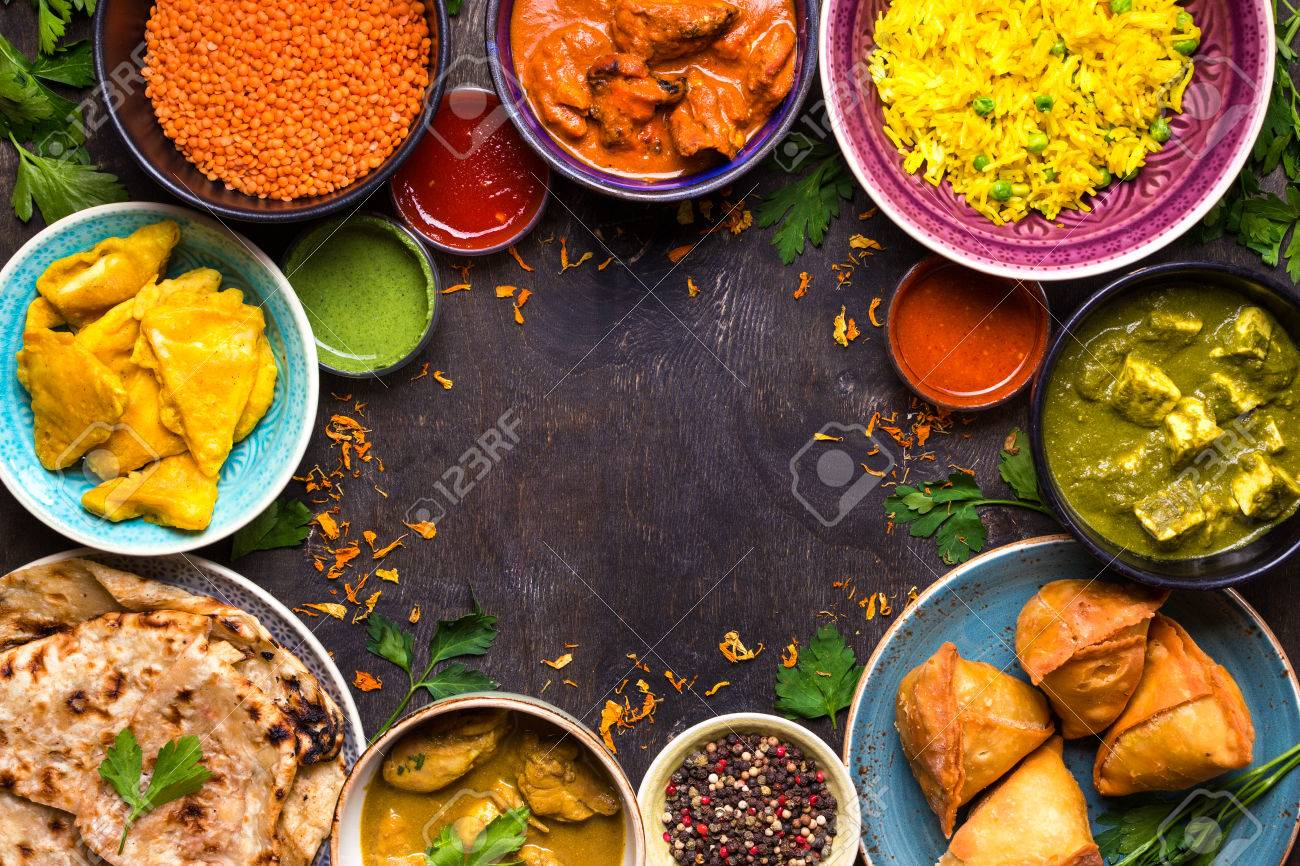 Assorted indian food on dark wooden background. Dishes of indian cuisine. Curry, butter chicken, rice, lentils, paneer, samosa, naan, chutney, spices. Space for text. Bowls and plates with indian food - 77145671