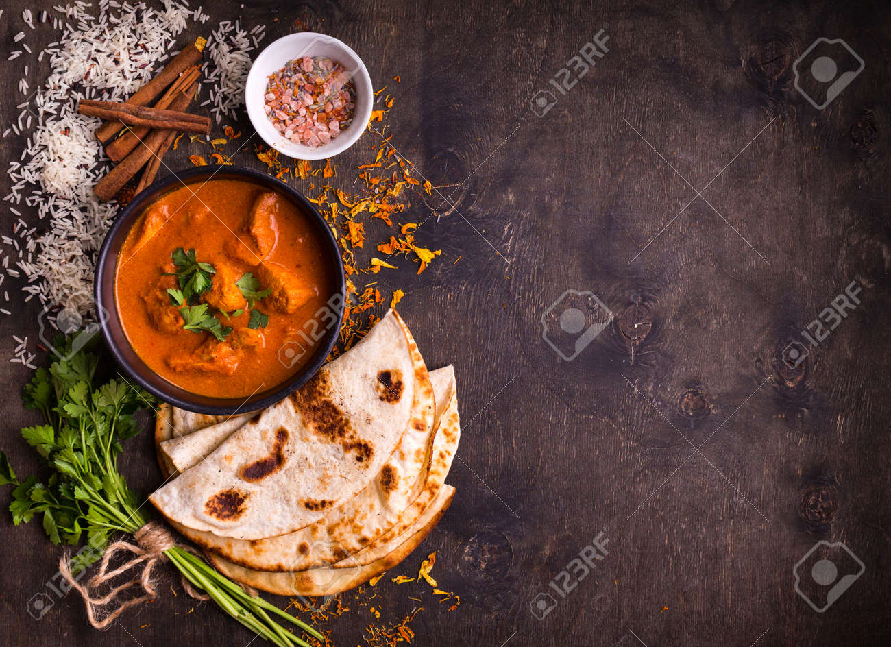 Spicy chicken tikka masala in bowl on rustic wooden background. With rice, indian naan butter bread, spices, herbs. Space for text. Traditional Indian/British dish. Top view. Indian food. Copy space - 76010848