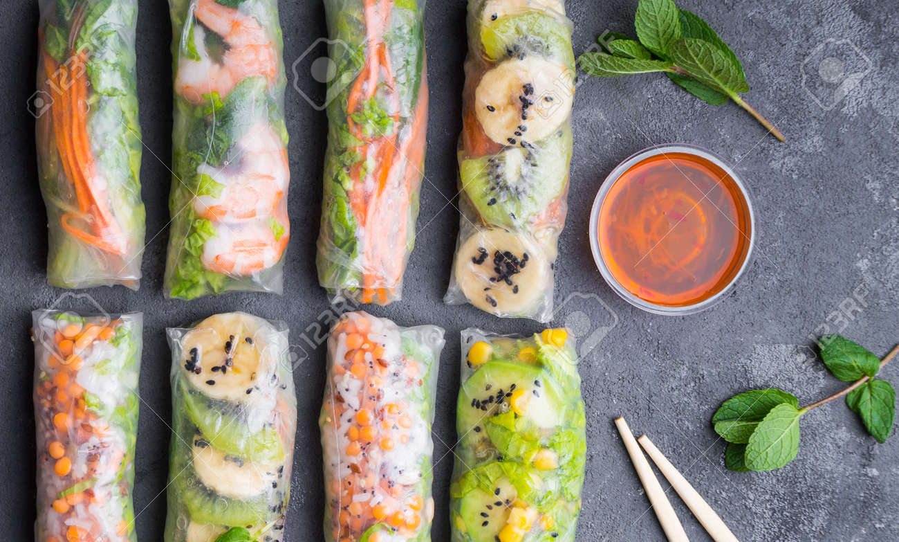 Fresh assorted spring rolls set. Handmade asian/Chinese spring rolls. Rustic concrete background. Spring rolls with shrimps, vegetables, fruits. Top view. Healthy asian food. Lunch/snacks/buffet - 80509607