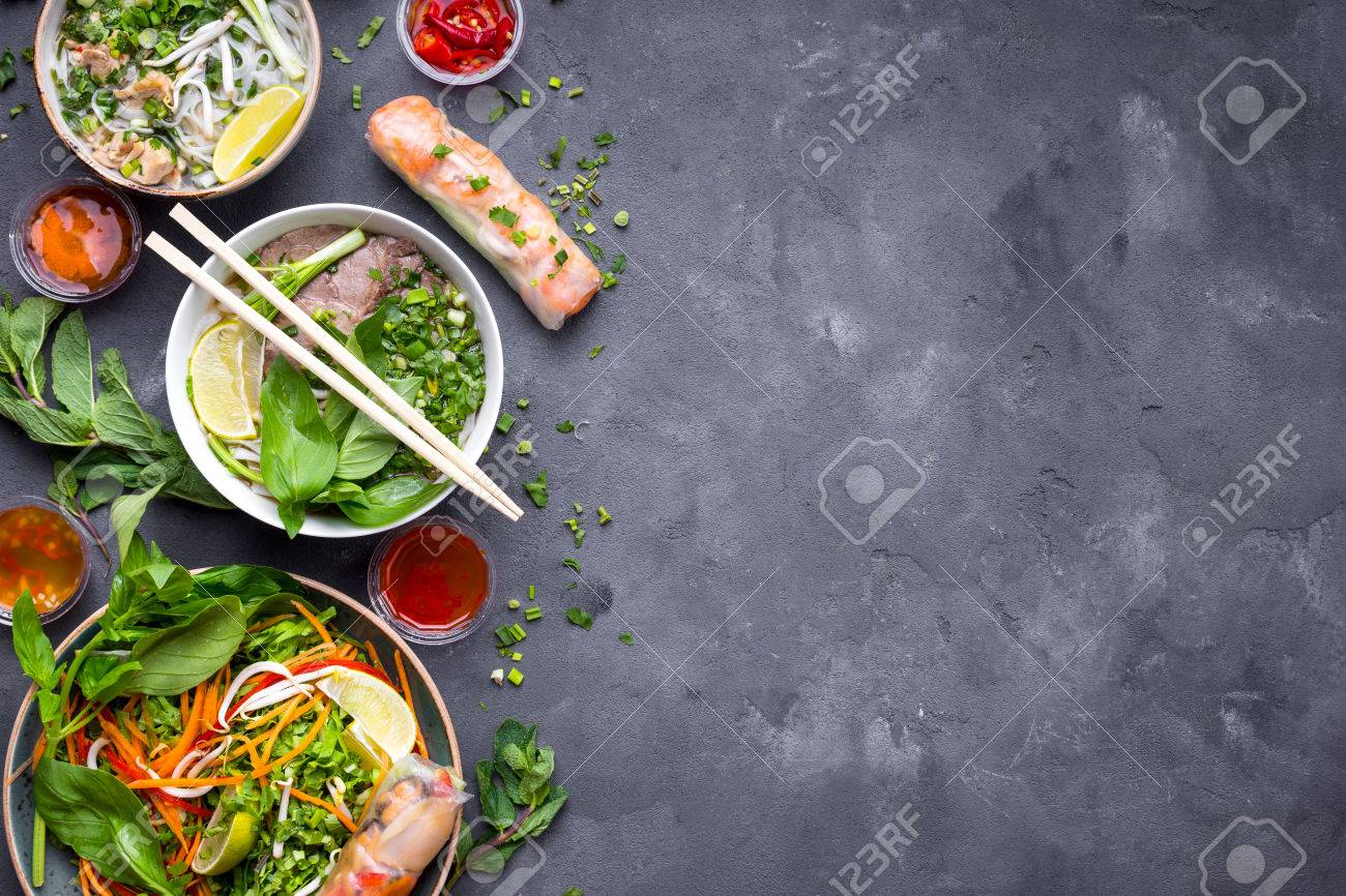 Assorted asian dinner, vietnamese food. Vietnamese noodle soup pho bo, pho ga, spring rolls, vegetable salad. Asian/vietnamese food background. Copy space. Traditional vietnamese dishes set. Top view - 80509605