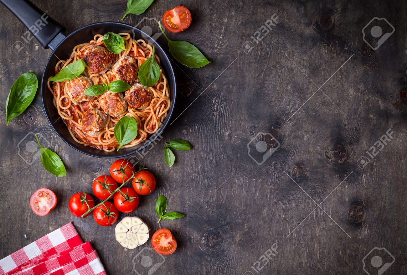 Spaghetti with meatballs, tomato sauce. Background. Italian American dish. Meatballs pasta in a pan. Space for text. Overhead. Traditional Italian cuisine. Dark rustic wooden table. Dinner with pasta - 84059833