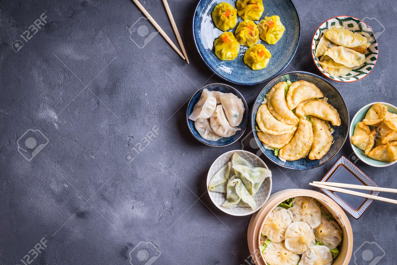Assorted dim sum appetizers on rustic background. Space for text. Chinese food for share. Buffet. Space for text. Traditional Chinese dim sum food. Top view. Different Chinese dumplings and appetizers - 84059861