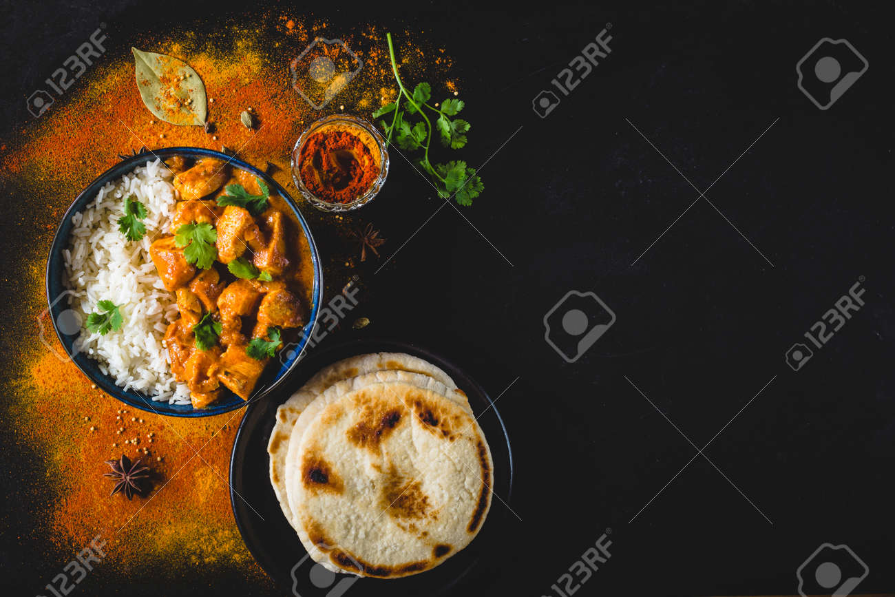 Indian Butter chicken with basmati rice in bowl, spices, naan bread. Black background. Space for text. Butter chicken, traditional Indian dish. Top view. Chicken tikka masala. Indian cuisine - 94113041