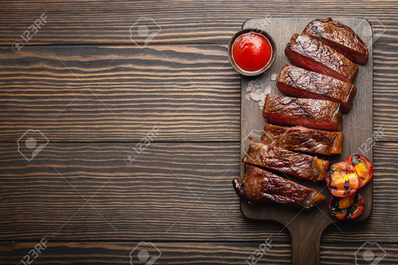 Grilled/fried and sliced marbled meat steak with fork, tomatoes, tomato sauce/ketchup on wooden cutting board, top view, close-up with space for text, rustic background. Beef meat steak concept - 128327204