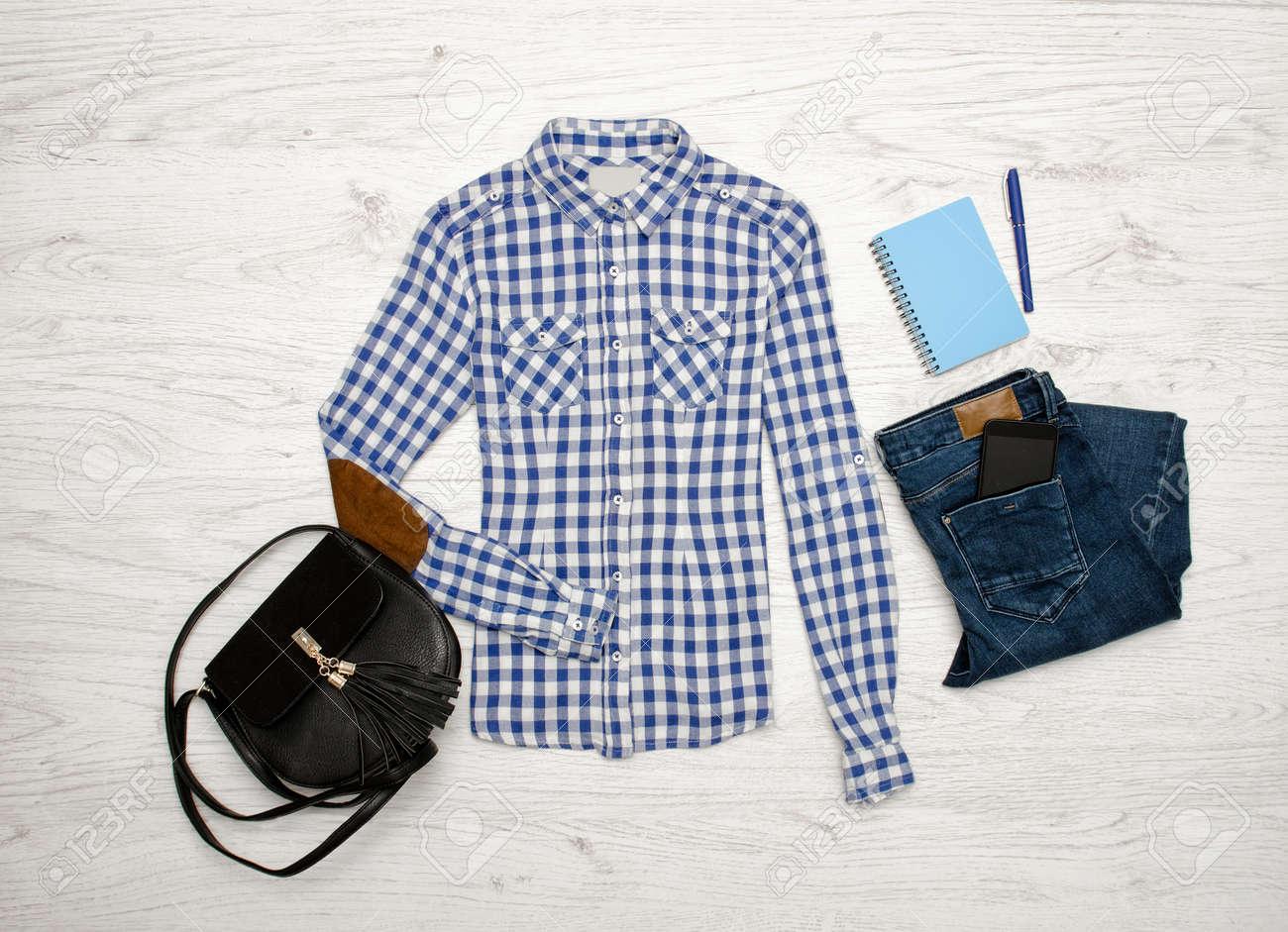comprare popolare b11a6 3129a Camicia a quadri blu e bianca, jeans, cellulare, taccuino con penna e borsa  nera. Fondo in legno Concetto alla moda, vista dall'alto