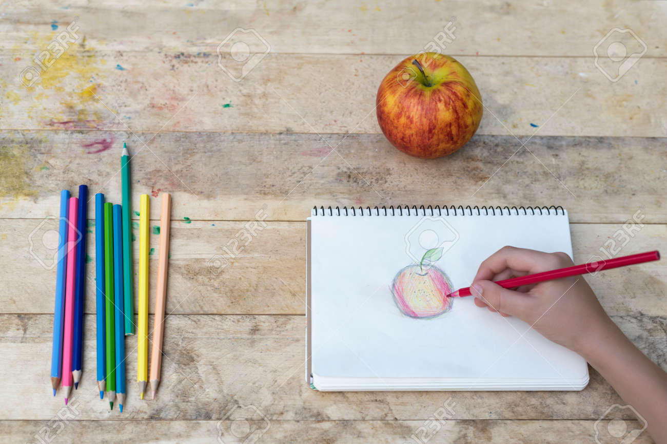Childrens hands draw an apple with colored pencils top view stock photo 112892053