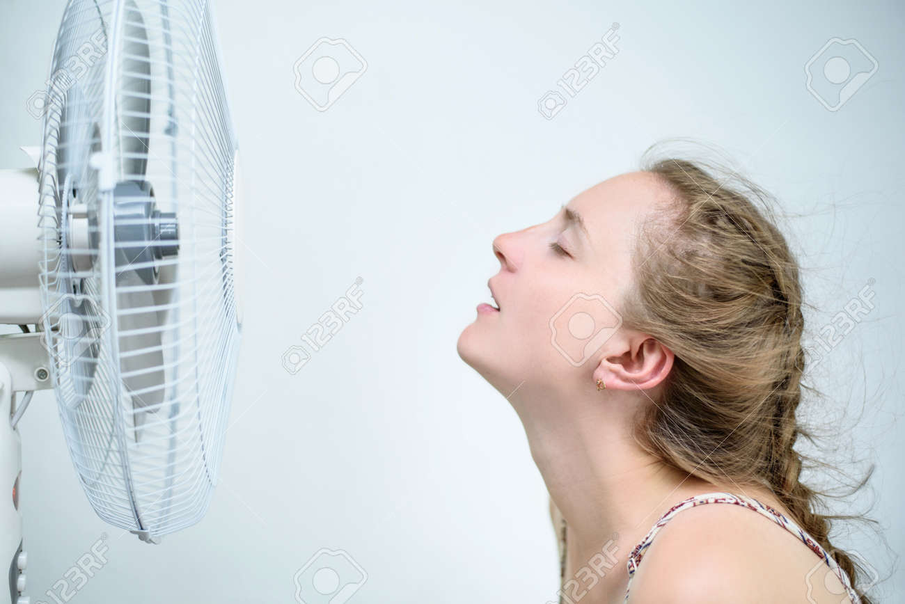 Young woman sitting under a fan with closed eyes from pleasure. Summer heat. White background - 121168611