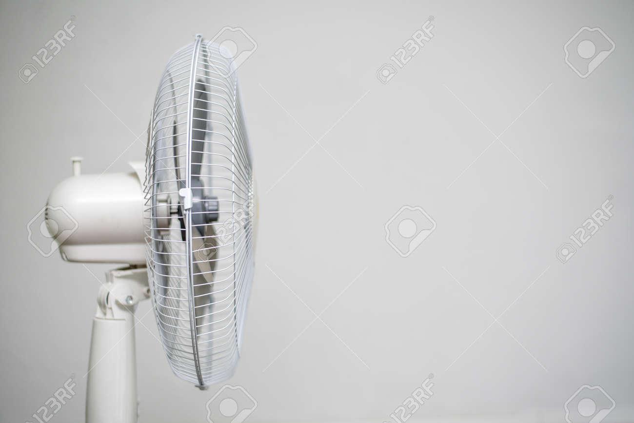 Floor fan standing on a gray wall background. - 128366241
