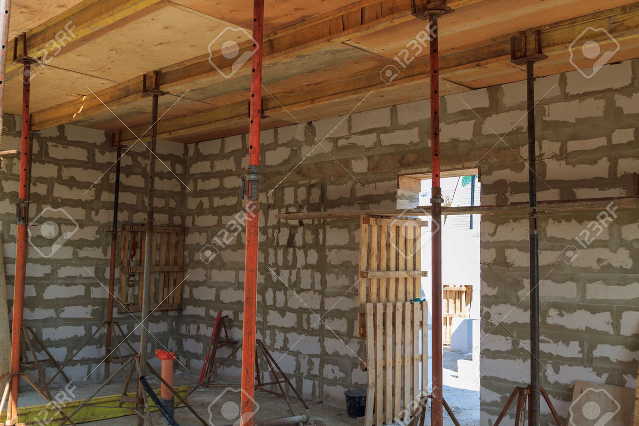 view of the wooden formwork with metal holders, which will be filled with the overlap between the floors in the country house under construction from the foam block - 150962589