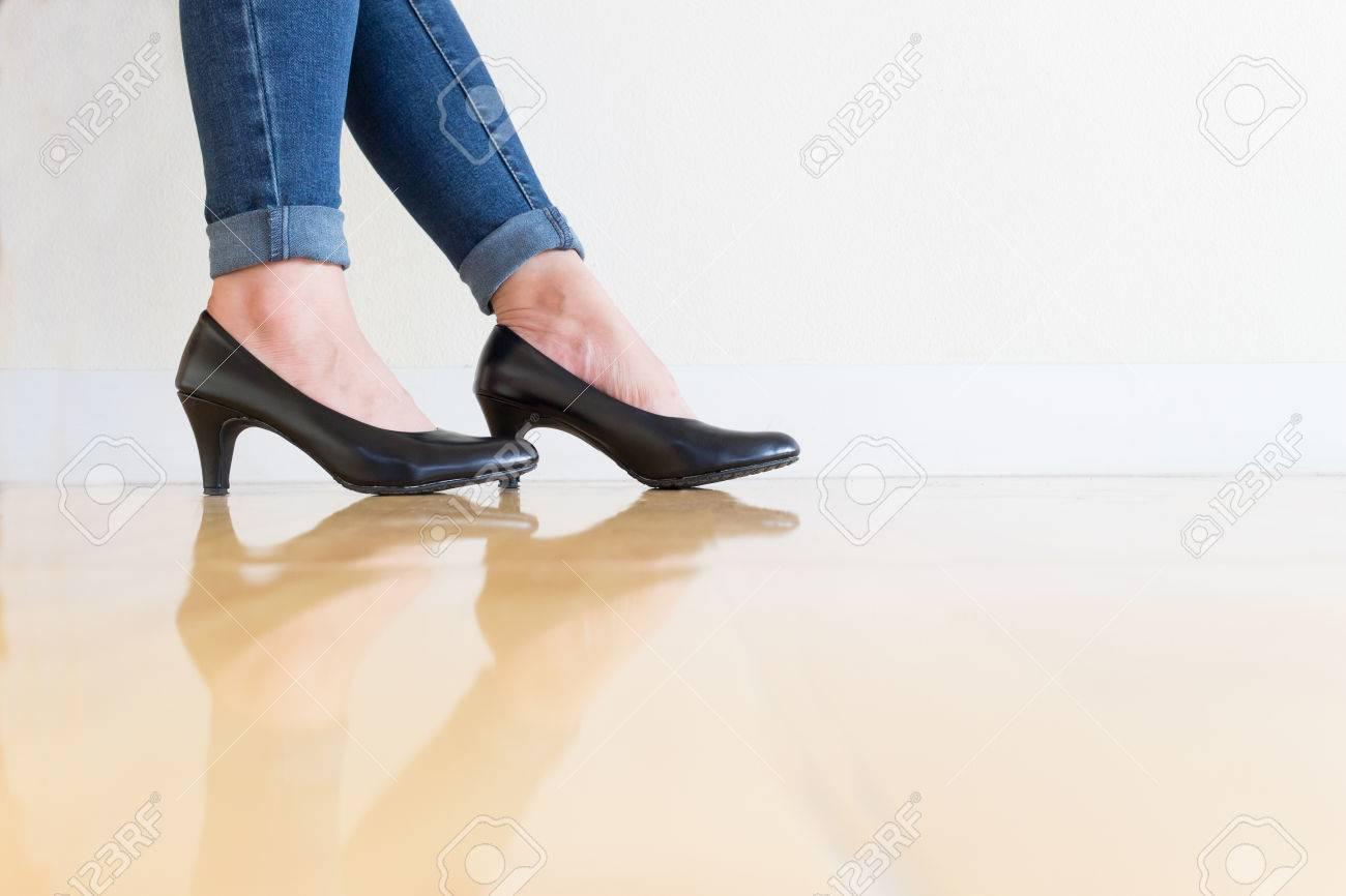 Jeune bureau femme bleu jeans Porter des chaussures à talons hauts, assis jambes croisées