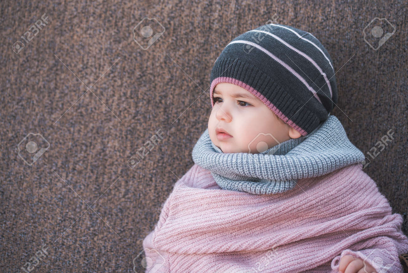 c3fcb2233 Cute Baby Girl Wearing A Warm Winter Hat And A Colorful Scarf ...