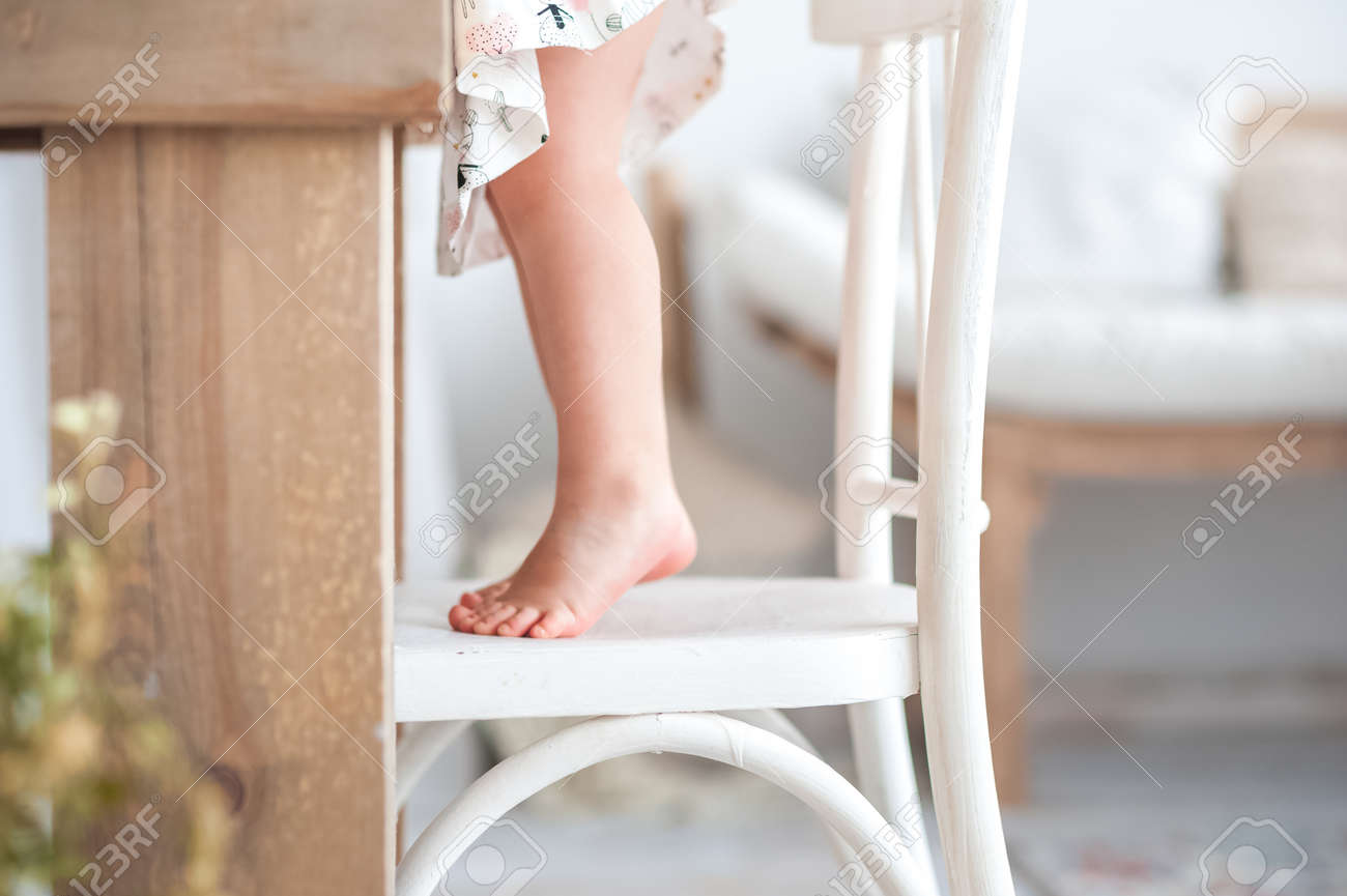 Baby little feet, feet on a white wooden kitchen chair in a rustic..