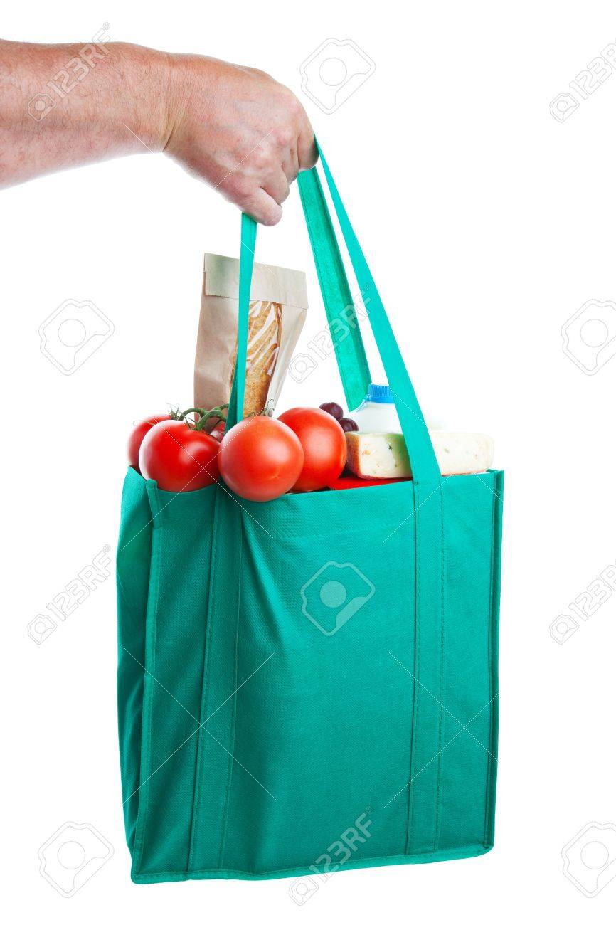 A strong hand holding an environmentally friendly bag full of groceries.  Shot on white background. Stock Photo - 5973658