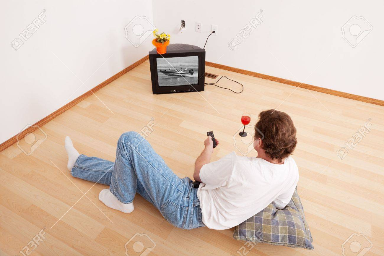 A middle-aged, newly divorced man, with little possessions in a new apartment, after his wife got everything in the divorce.  Image on television is my own and of the same model. Stock Photo - 6877682
