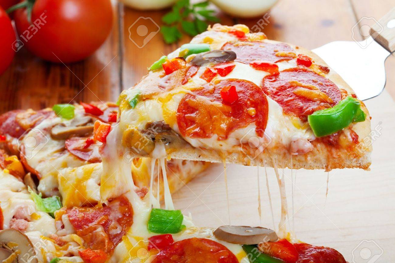 A slice of hot pizza deluxe with pepperoni, mushrooms, peppers, & lots of gooey mozzarella cheese, ready to be served. Stock Photo - 7573425