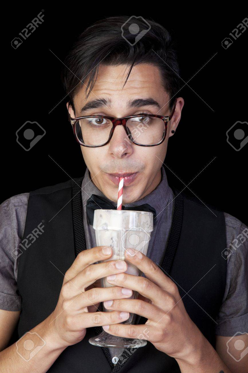 A geeky, nerd guy sucking chocolate milkshake through a straw Stock Photo - 14942834