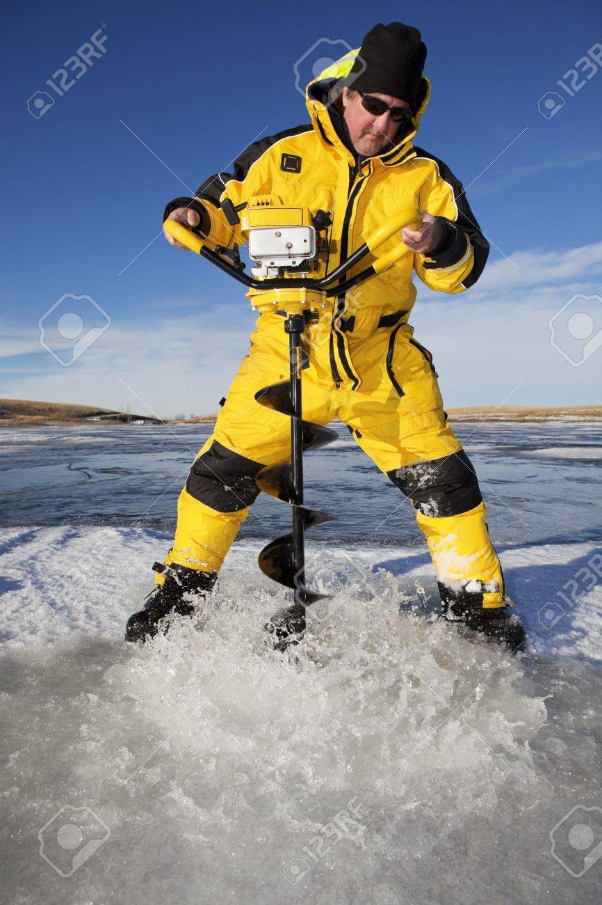 Water floods over the ice as an ice fisherman drills through with an auger to make his fishing hole Stock Photo - 17797259