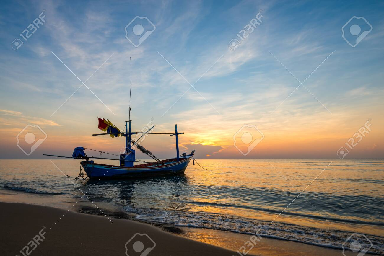 Colorful sky at sunrise on the sea beach with fishing boat. silhouette - 122276436