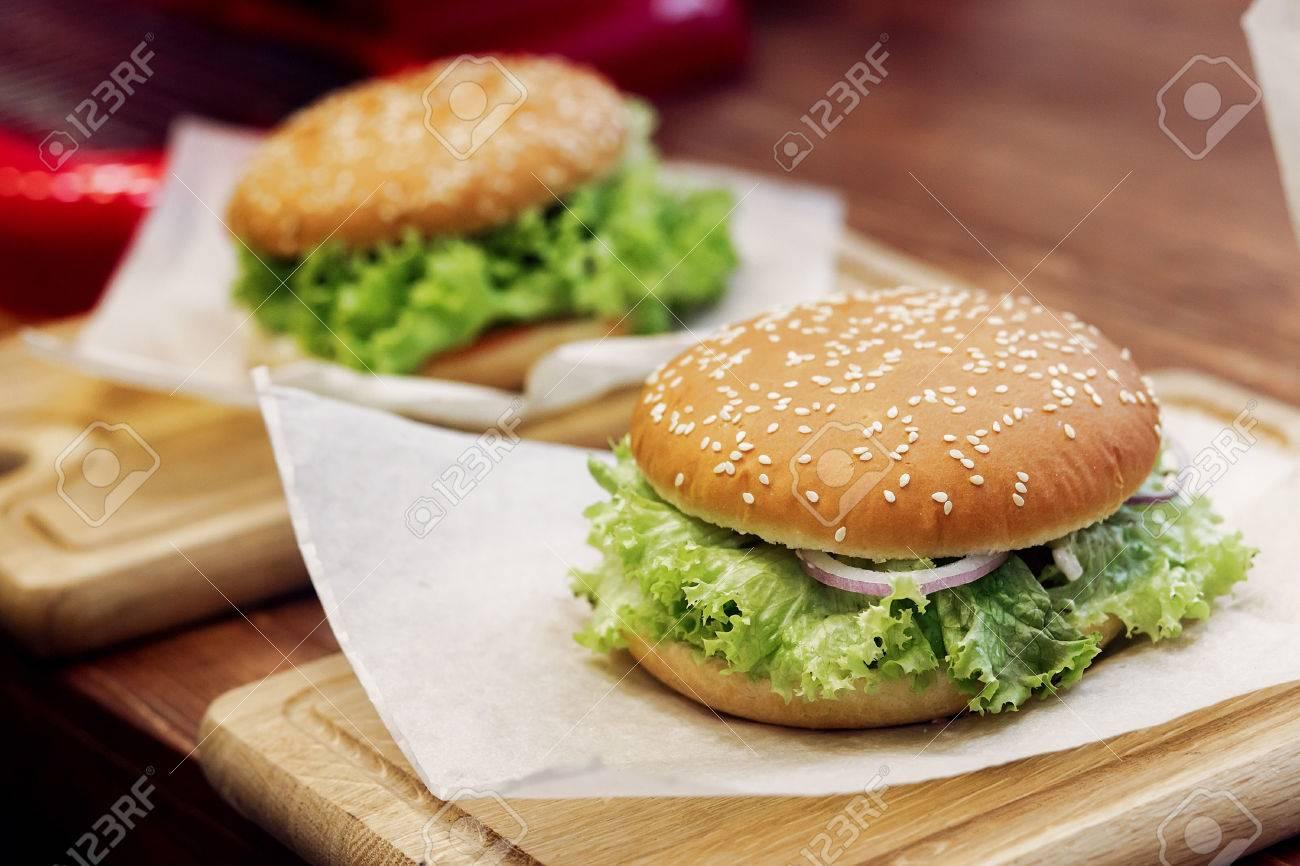Travailleur de sexe masculin mangeant l hamburger dans le bureau