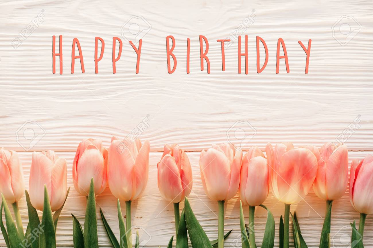 Happy Birthday Text Sign On Pink Tulips White Rustic Wooden Background Flat Lay Spring