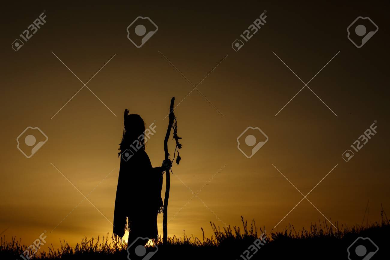 silhouette of native american shaman with pikestaff on background of sunset beutiful in mountains - 75147099